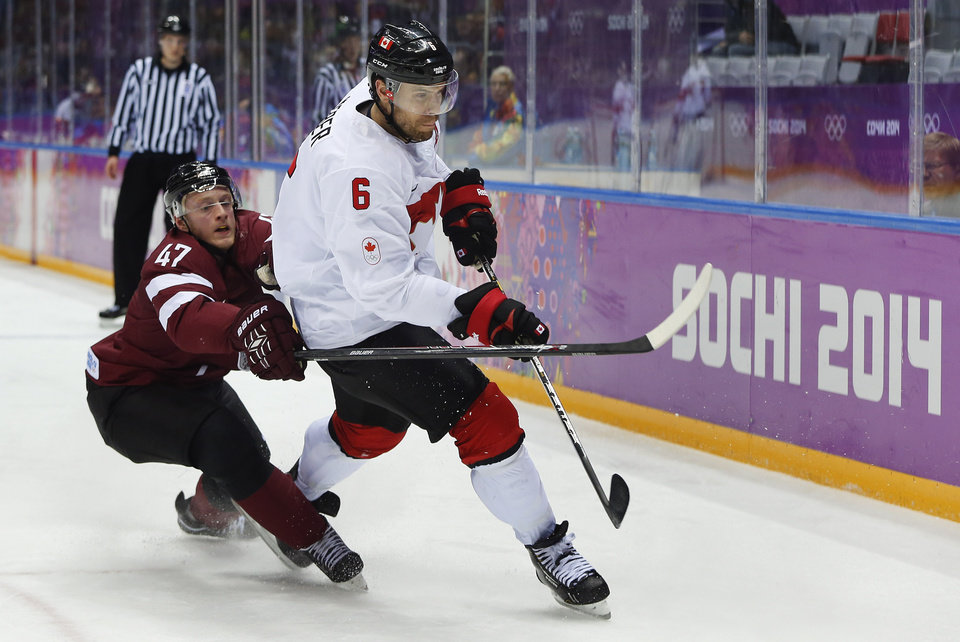 Photo - Latvia forward Martins Cipulis reaches around Canada defenseman Shea Weber during the second period of a men's quarterfinal ice hockey game at the 2014 Winter Olympics, Wednesday, Feb. 19, 2014, in Sochi, Russia. (AP Photo/Julio Cortez)