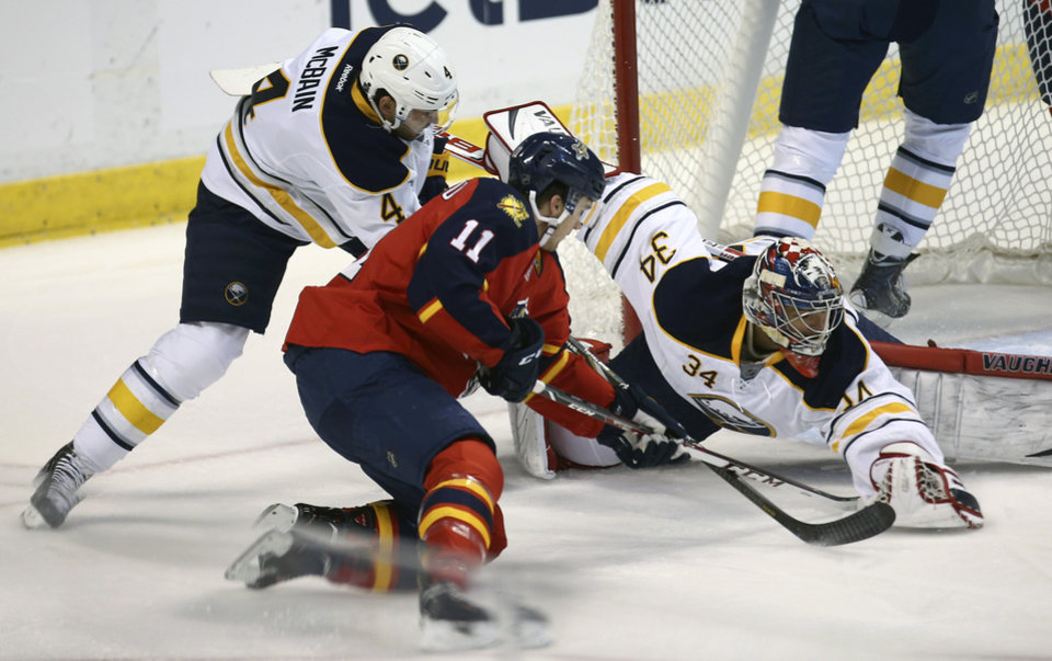 Photo - Florida Panthers' Jonathan Huberdeau (11) tries to score as Buffalo Sabres goalie Michael Neuvirth (34) and Jamie McBain (4) try to block the shot during the first period of an NHL hockey game in Sunrise, Fla., Friday, March 7, 2014. (AP Photo/J Pat Carter)