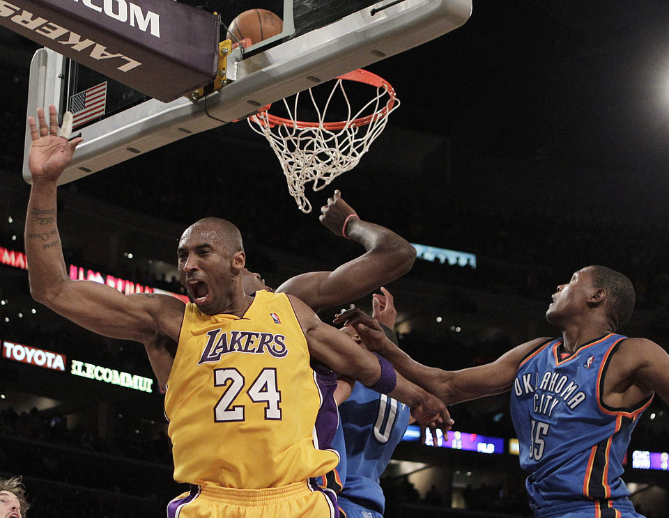 Photo - FOUL: Los Angeles Lakers guard Kobe Bryant, left, reacts after he was fouled by the Oklahoma City Thunder during the second half of Game 2 in a first-round NBA basketball playoff series in Los Angeles, Tuesday, April 20, 2010. Oklahoma City Thunder forward Kevin Durant, right, watches. The Lakers won 95-92. (AP Photo/Jae C. Hong) ORG XMIT: LAS213