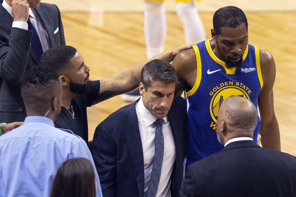 Photo - Golden State Warriors forward Kevin Durant, right, is consoled by Drake as he walks off the court after sustaining an injury during first half basketball action in Game 5 of the NBA Finals against Toronto Raptors in Toronto, Monday, June 10, 2019. (Chris Young/The Canadian Press via AP)