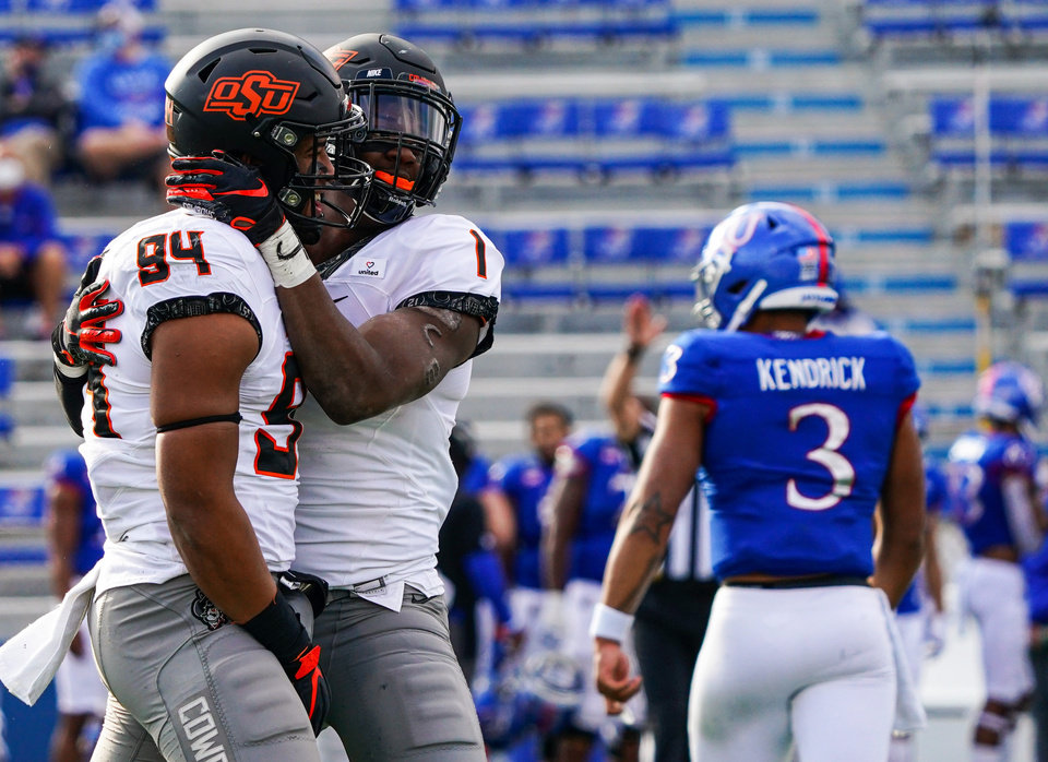 Photo - Oct 3, 2020; Lawrence, Kansas, USA; Oklahoma State Cowboys defensive end Trace Ford (94) is congratulated by linebacker Calvin BundageÊ (1) after sacking Kansas Jayhawks quarterback Miles Kendrick (3) during the second half at David Booth Kansas Memorial Stadium. Mandatory Credit: Jay Biggerstaff-USA TODAY Sports