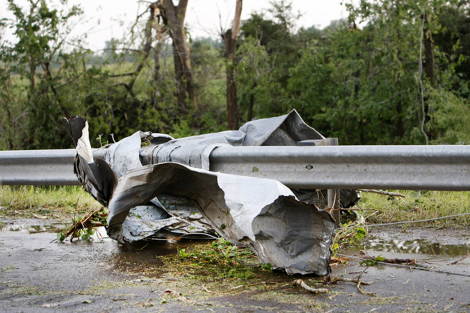 Sheet metal is wrapped around a guard rail on Harrah Road south of Reno after a tornado whipped through the area Monday afternoon. Photo by Hugh Scott, The Oklahoman