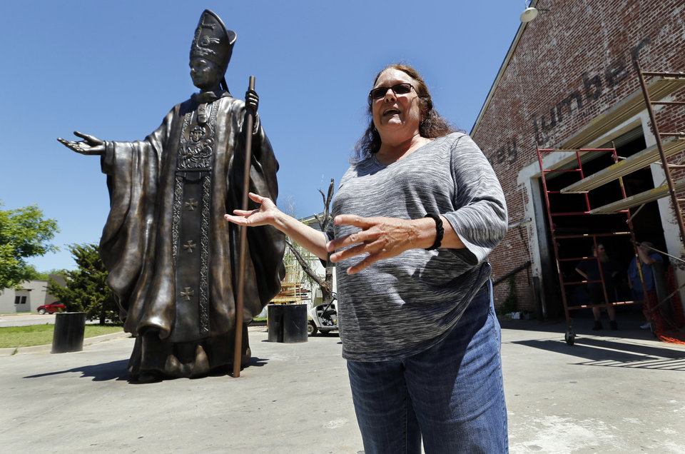Photo -  Artist Teresa Clark talks about her 21-foot statue of Pope John Paul II outside The Crucible in Norman, where it was forged. [PHOTO BY STEVE SISNEY, THE OKLAHOMAN]