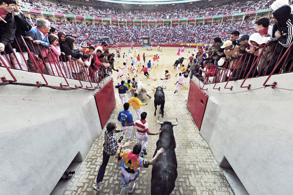 Revelers run to the bullring Friday during the fourth run of the Jandilla fighting bulls at the San Fermin Fiestas in Pamplona, northern Spain.  AP Photo