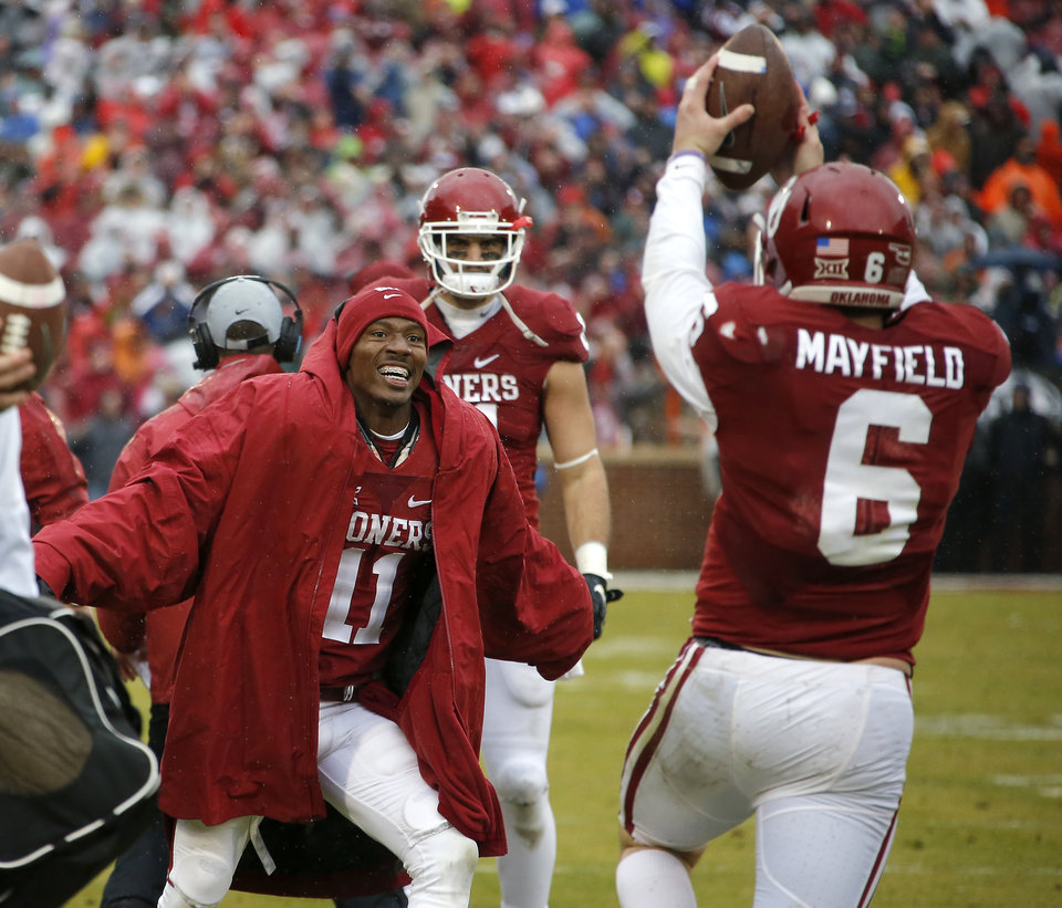 Photo - Oklahoma's Dede Westbrook (11) celebrates with Oklahoma's Baker Mayfield (6) after a Oklahoma's Joe Mixon touchdown late in the fourth quarter of the Bedlam college football game between the Oklahoma Sooners (OU) and the Oklahoma State Cowboys (OSU) at Gaylord Family - Oklahoma Memorial Stadium in Norman, Okla., Saturday, Dec. 3, 2016. Oklahoma won 38-20. Photo by Bryan Terry, The Oklahoman