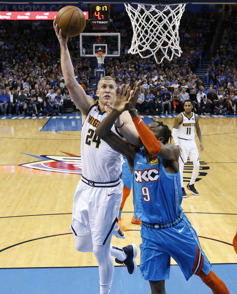 Photo - Denver Nuggets forward Mason Plumlee (24) shoots over Oklahoma City Thunder forward Jerami Grant (9) during the second half of an NBA basketball game Friday, March 29, 2019, in Oklahoma City. (AP Photo/Sue Ogrocki)