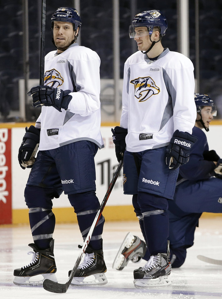 Photo - Nashville Predators defenseman Roman Josi, right, of Switzerland, talks with captain Shea Weber, left, at NHL hockey training camp on Wednesday, Jan. 16, 2013, in Nashville, Tenn. The shortened, 48-game season begins Saturday, Jan. 19. (AP Photo/Mark Humphrey)