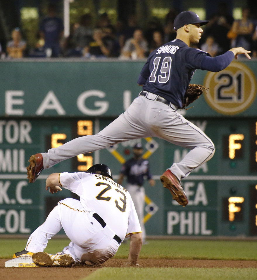 Photo - Atlanta Braves shortstop Andrelton Simmons hops over Pittsburgh Pirates' Travis Snider to complete a double play on Chris Stewart in the fifth inning of the baseball game on Wednesday, Aug. 20, 2014, in Pittsburgh. (AP Photo/Keith Srakocic)