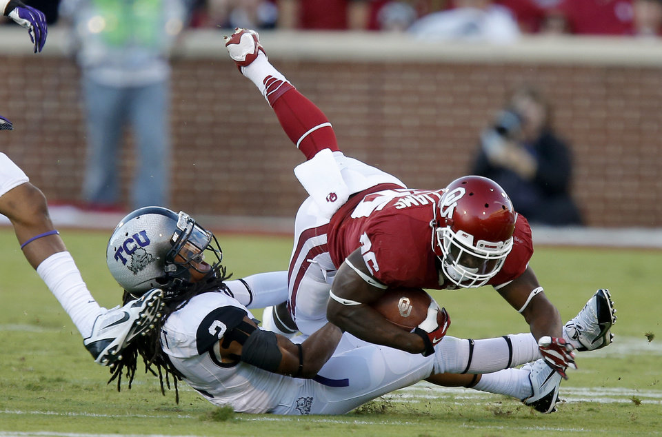 Photo - Oklahoma's Damien Williams (26) is brought down by TCU's Jason Verrett (2) during a college football game between the University of Oklahoma Sooners (OU) and the TCU Horned Frogs at Gaylord Family-Oklahoma Memorial Stadium in Norman, Okla., on Saturday, Oct. 5, 2013. Photo by Bryan Terry, The Oklahoman