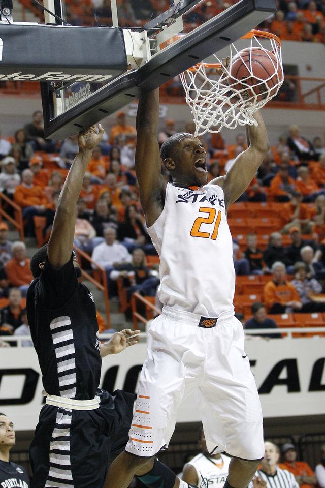 Oklahoma State forward Kamari Murphy dunks in front of Portland State guard Marcus Hall, left, in the first half of an NCAA college basketball game in Stillwater, Okla., Sunday, Nov. 25, 2012. (AP Photo/Sue Ogrocki)
