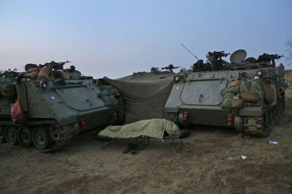 An Israeli soldier sleeps next to an armoured personnel carriers at a staging area near the Israel Gaza Strip Border, southern Israel, early Tuesday, Nov. 20, 2012. On Tuesday, grieving Gazans were burying militants and civilians killed in ongoing Israeli airstrikes, and barrages of rockets from Gaza sent terrified Israelis scurrying to take cover. Efforts to end a week-old convulsion of Israeli-Palestinian violence drew in the world\'s top diplomats Tuesday, with U.S. President Barack Obama dispatching his secretary of state to the region on an emergency mission and the U.N. chief appealing from Cairo for an immediate cease-fire. (AP Photo/Lefteris Pitarakis)