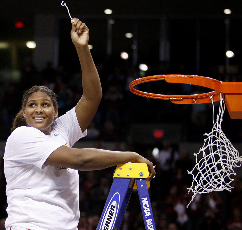 Photo - OU's Courtney Paris cuts down the net after the NCAA women's basketball regional  tournament finals between Oklahoma and Purdue at the Ford Center in Oklahoma City, Tuesday, March 31, 2009.  OU won, 74-68. Photo by Bryan Terry, The Oklahoman