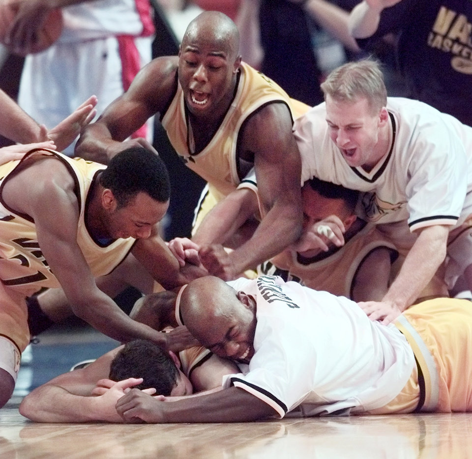 NCAA MIDWEST REGIONAL BASKETBALL TOURNAMENT AT THE MYRIAD: Valparaiso players smother the player who scored at the buzzer, Bryce Drew, to defeat the University of Mississippi in basketball.