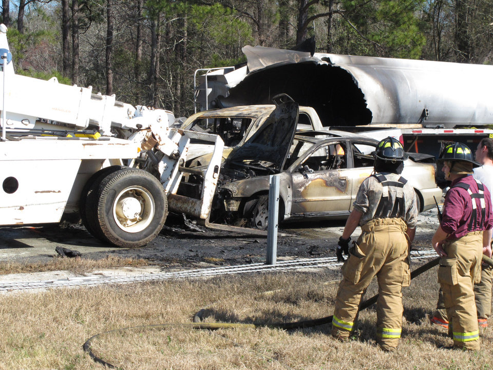 Photo - Firefighters stand by as a forklift moves a smashed and burned car at the scene where 27 vehicles collided Wednesday, Feb. 6, 2013, on Interstate 16 near Montrose, Ga.  More than two dozen cars, pickup trucks and tractor-trailers collided Wednesday morning in a fiery pileup on a foggy Georgia interstate 16, killing at least three people and sending nine others to a hospital, officials said. (AP Photyo/Russ Bynum)