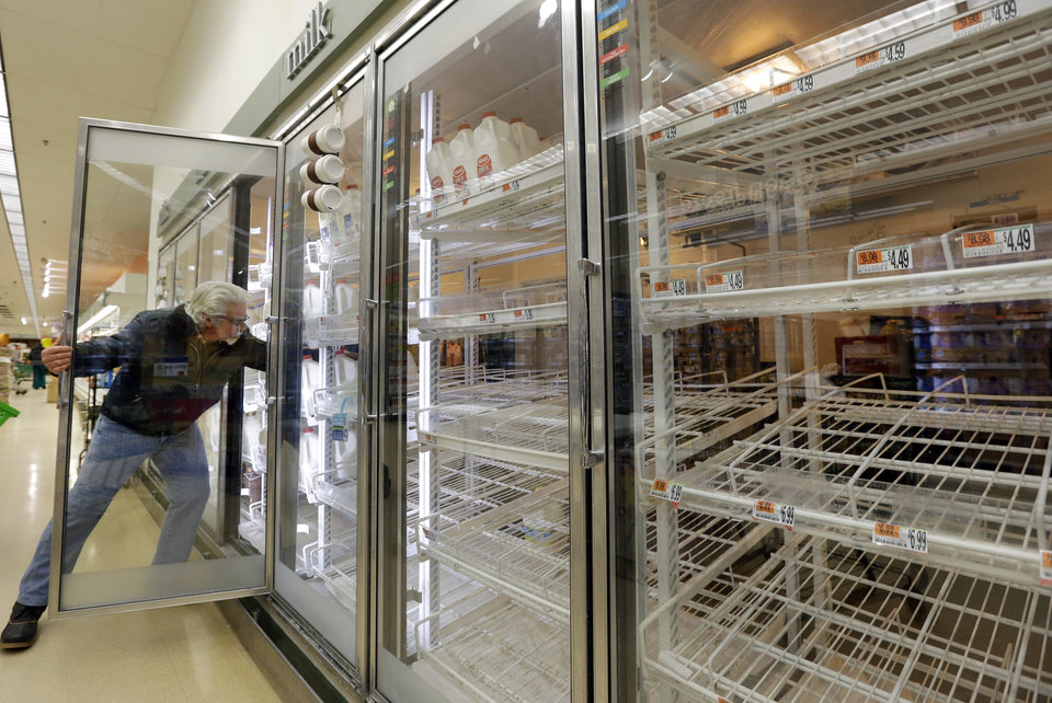 Jack Percoco of Cambridge, Mass. reaches into depleted shelves for milk at a supermarket in Somerville, Mass., Friday, Feb. 8, 2013. A major winter storm is heading toward the U.S. Northeast with up to 2 feet of snow expected for a Boston-area region that has seen mostly bare ground this winter. (AP Photo/Elise Amendola) ORG XMIT: MAEA101