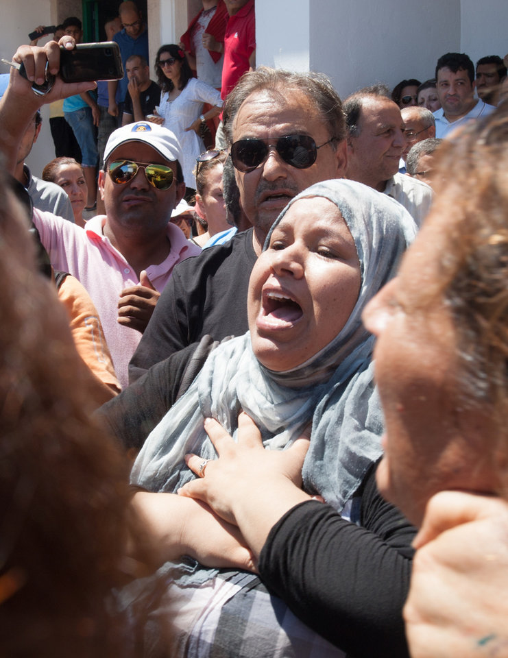 Photo - A Tunisian supporter of the Popular Front party reacts at Mahmoud Materi hospital, after Mohammed Brahmi died from his wounds after he was shot to death in his car outside his home, north of Tunis, Tunisia, Thursday, July 25, 2013. Brahmi, 58, of an Arab nationalist political party was in his car outside home when gunmen fired several shots at him, said Interior Ministry spokesman Mohammed Ali Aroui. It is the second killing of an opposition member this year, following that of Chokri Belaid, a member of the same leftist Popular Front coalition as Brahmi. Belaid was also shot dead in his car outside his home in February. His killing provoked a political crisis that nearly derailed Tunisia's political transition. (AP Photo/Amine Landoulsi)