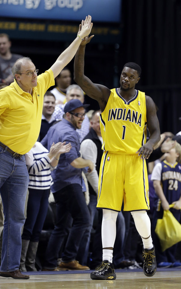 Photo - Indiana Pacers guard Lance Stephenson celebrates with a fan in the closing second of the second half of an NBA basketball game in Indianapolis, Saturday, Feb. 1, 2014. The Pacers defeated the Nets 97-96. (AP Photo/Michael Conroy)