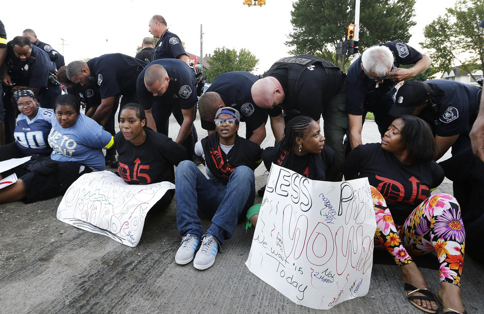 Photo - Police handcuff protesters blocking traffic on Mack Avenue in Detroit as part of a national protest to push fast-food chains to pay their employees at least $15 an hour Thursday, Sept. 4, 2014. Hundreds of workers from McDonald's, Taco Bell, Wendy's and other fast-food chains are expected to walk off their jobs Thursday, according to labor organizers of the latest national protest to push the companies to pay their employees at least $15 an hour. (AP Photo/Paul Sancya)