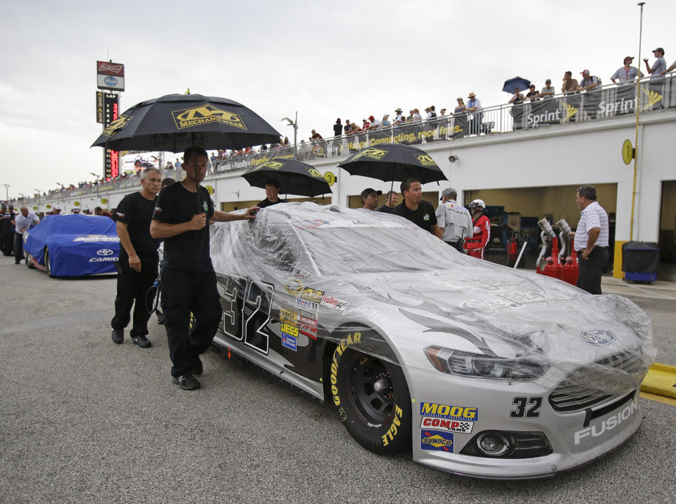 Photo - Terry Labonte's crew pushes his car through the garage area after qualifying for the NASCAR Sprint Cup Series auto race was shortened due to rain at Daytona International Speedway in Daytona Beach, Fla., Friday, July 4, 2014. (AP Photo/John Raoux)