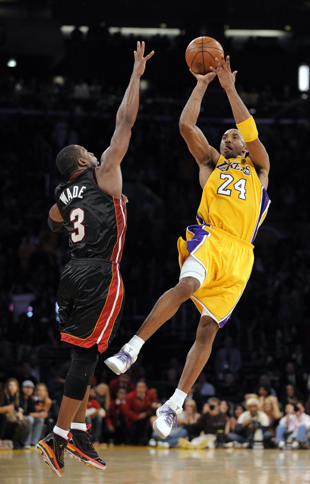 Photo - Los Angeles Lakers guard Kobe Bryant, right, makes a last second, three point basket to win the game as Miami Heat guard Dwyane Wade defends during the second half of their NBA basketball game, Friday, Dec. 4, 2009, in Los Angeles. The Lakers won 108-107.  (AP Photo/Mark J. Terrill) ORG XMIT: LAS110