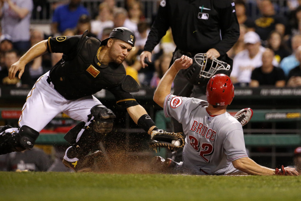 Photo - Pittsburgh Pirates catcher Russell Martin tags out Cincinnati Reds' Jay Bruce (32) during the eighth inning of a baseball game in Pittsburgh Monday, April 21, 2014. Bruce was attempting to score the second run on a RBI single by teammate Devin Mesoraco. The play was reviewed and the out call was upheld. (AP Photo/Gene J. Puskar)