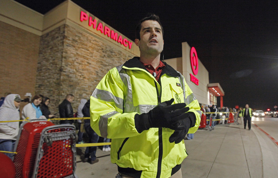 Photo - Hunter Witt, Assets Protection leader at Target, supervises the midnight opening on Black Friday, Nov. 25, 2011, in Moore, Okla. Photo by Steve Sisney, The Oklahoman