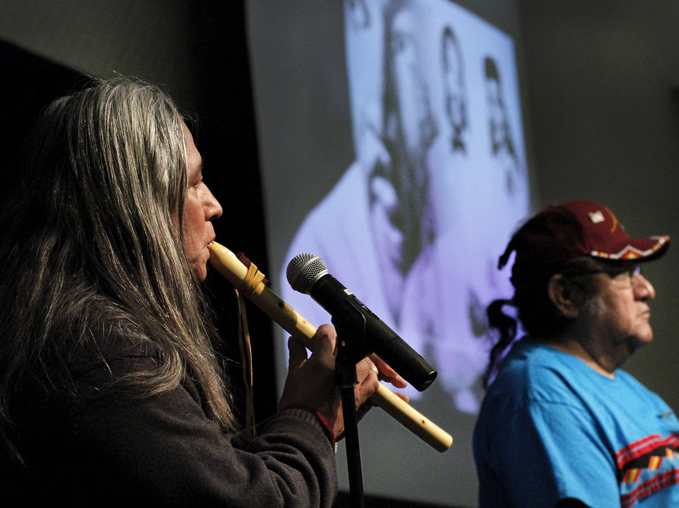 Photo - Albert Gray Eagle plays a flute while Matt Hamilton waits to deliver a prayer of benediction during the 16th annual Midwest City Dr. Martin Luther King, Jr. Prayer Breakfast inside the Reed Conference Center Monday morning, Jan. 21, 2013. Both men are members of the Cheyenne/Sioux tribe. The theme of this year's event is