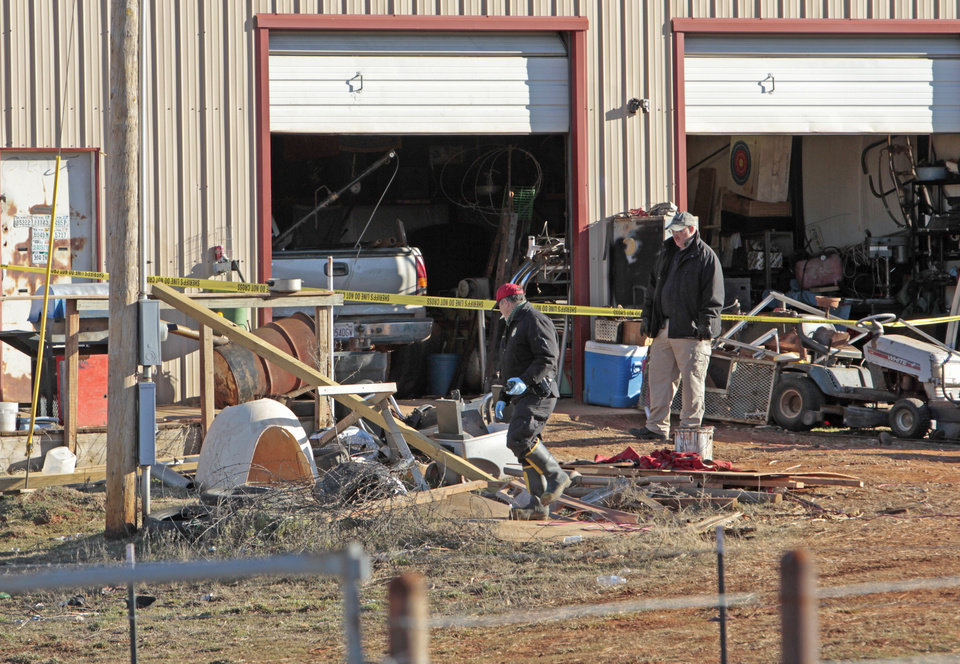 Cleveland County deputies and the fire marshall examine the scene of a car fire in the 20000 block of east Etowah Road where deputies earlier shot a suspect on Friday, Jan. 6, 2012, in Noble, Okla.  Photo by Steve Sisney, The Oklahoman
