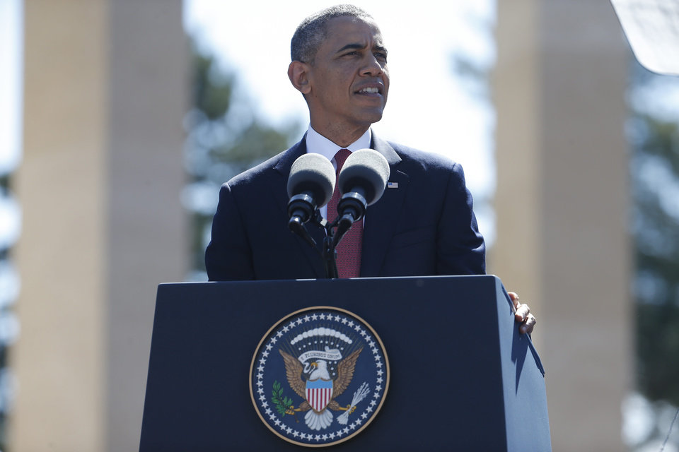 Photo - U.S. President Barack Obama  speaks at Normandy American Cemetery at Omaha Beach as he participates in the 70th anniversary of D-Day in Colleville sur Mer in Normandy, France, Friday, June 6, 2014. (AP Photo/Charles Dharapak)