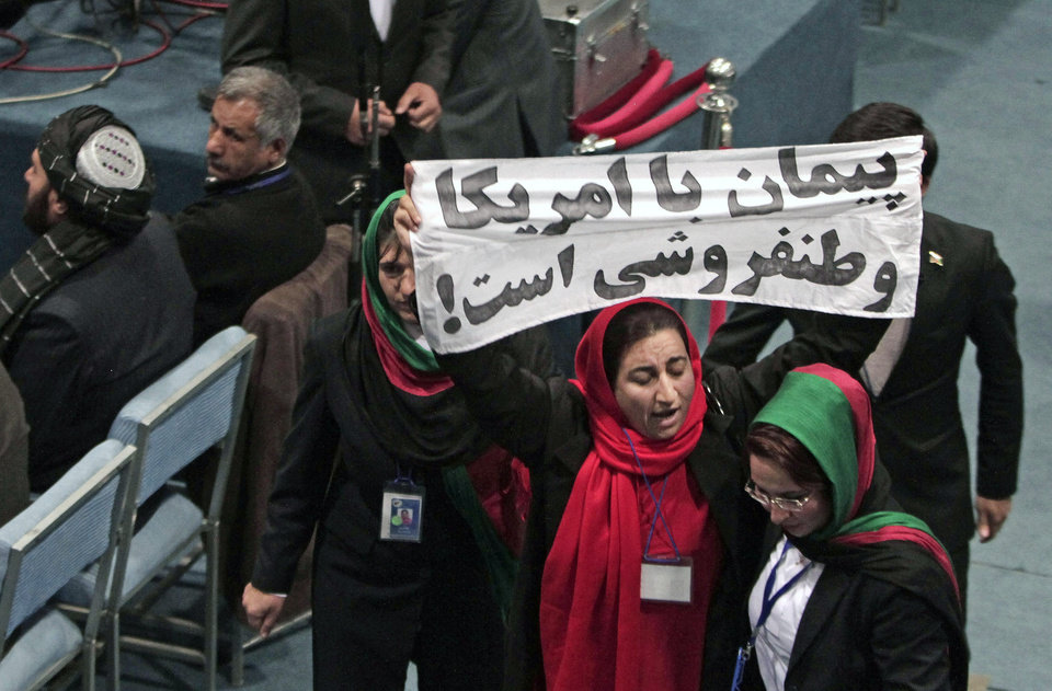 Photo - A member of the Afghan Loya Jirga holds a banner with Dari that reads,