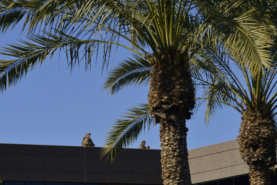 Photo - SWAT police officers inspect the roof of an office building after a shooting at the building in Phoenix on Wednesday, Jan. 30, 2013. A gunman opened fire at the Phoenix office building, wounding three people, one of them critically, authorities said. Police were searching for the shooter. (AP Photo/Patrick Sison)