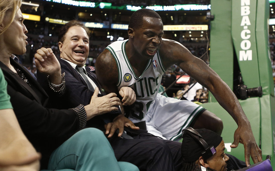 Photo - Boston Celtics' Brandon Bass lands in the lap of Boston Celtics co-owner Stephen Pagliuca during the second quarter of Game 3 of a first round NBA basketball playoff series against the New York Knicks, Friday, April 26, 2013, in Boston. (AP Photo/Winslow Townson)