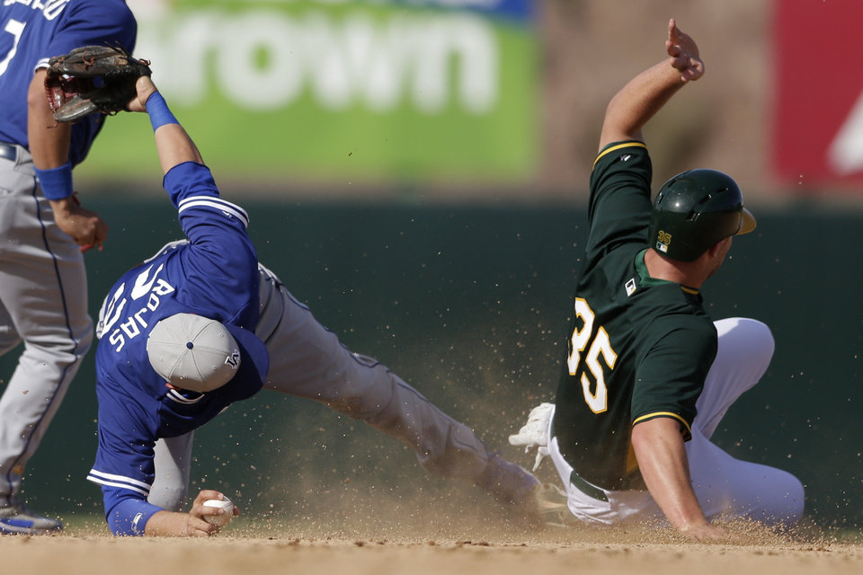Photo - Los Angeles Dodgers shortstop Miguel Rojas, left, reaches with his foot towards second base as Oakland Athletics' Chris Gimenez, right, is caught stealing second  during the seventh inning of a spring training baseball game Monday, March 3, 2014, in Phoenix. (AP Photo/Gregory Bull)