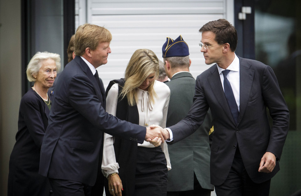 Photo - Dutch King Willem-Alexander, left, shakes hands with Dutch Prime Minister Mark Rutte, right, as they leave a meeting together with Queen Maxima, center, in Nieuwegein, near the central city of Utrecht, Netherlands, Monday, July 21, 2014. Relatives of Dutch victims killed in the downing of Malaysia Airlines Flight 17 were meeting Monday afternoon with their king, queen and prime minister amid growing anger at the treatment of their loved ones' bodies by pro-Russian rebels in Ukraine. In an unusual move that underscored the severity of the national trauma, a somber King Willem-Alexander gave a brief televised address to his country after meeting grieving relatives. 'This terrible disaster has left a deep wound in our society,' the king said. 'The scar will be visible and tangible for years to come.' (AP Photo/Phil Nijhuis)