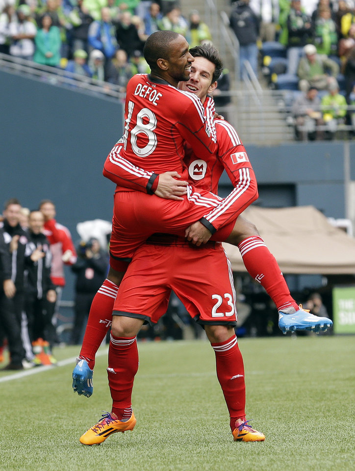 Photo - Toronto FC's Jermain Defoe (18) is lifted by teammate Alvaro Rey (23) after scoring his second of two goals in the first half of an MLS soccer match against the Seattle Sounders, Saturday, March 15, 2014, in Seattle. (AP Photo/Ted S. Warren)