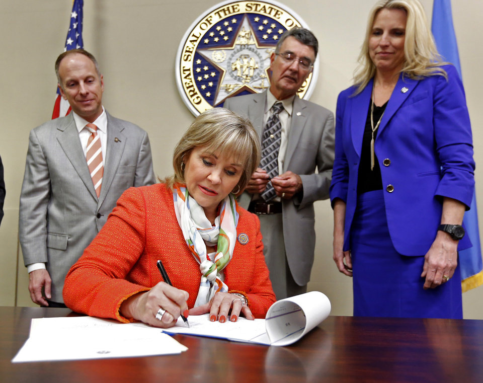 Photo - State Speaker of the House Jeff Hickman, Rep. Doug Cox and Sen. A.J. Griffin stand behind Gov. Mary Fallin on Tuesday as she signs a prescription drug bill into law at the state Capitol.  Photo by Steve Sisney, The Oklahoman  STEVE SISNEY -  THE OKLAHOMAN