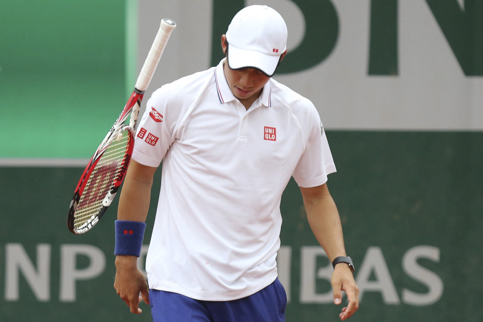 Photo - Japan's Kei Nishikori throws his racket after missing a return during the first round match of the French Open tennis tournament against Slovakia's Martin Klizan at the Roland Garros stadium, in Paris, France, Monday, May 26, 2014. Nishikori lost in three sets 6-7, 1-6, 2-6. (AP Photo/David Vincent)