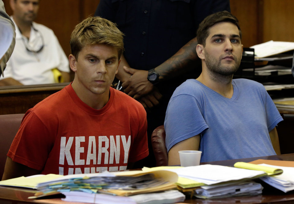 Photo - Bryan Caputo, left, and Daniel Petryszyn sit during arraignment proceedings in New York state Supreme Court,  Wednesday, July 23, 2014. They are two of six people who were indicted Wednesday in an international ring that took over more than 1,600 StubHub users' accounts and fraudulently bought tickets to such prime events as Jay-Z and Elton John concerts and Broadway shows like