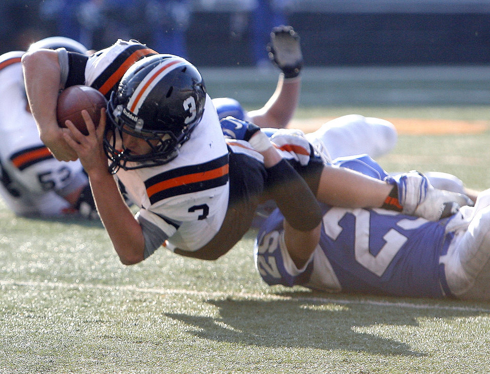 Wayne's Louden Johnson dives forward as Woodland's Tracey Wilson tackles him during the Class A state championship high school football game at Boone Pickens Stadium in Stillwater, Okla., Saturday, Dec. 10, 2011. Photo by Sarah Phipps, The Oklahoman