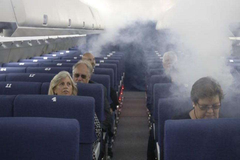 Photo -  FAA employees on Thursday participate in a demonstration of an airline cabin filling with smoke, in a simulator at the FAA Civil Aerospace Medical Institute in the Mike Monroney Aeronautical Center. [AP PHOTO]