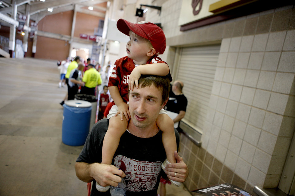 Photo - 23-month old Jax Payne, of Houston, sits on his father Jackson Payne's shoulders as they wait in line during the University of Oklahoma's Meet the Sooners Day at Gaylord Family-Oklahoma Memorial Stadium in Norman, Okla., Saturday, August 6, 2011. Photo by Bryan Terry, The Oklahoman