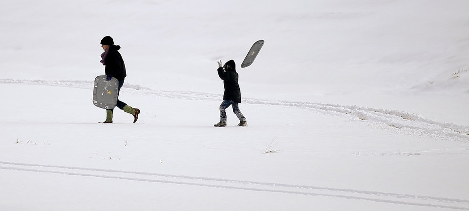 People walk up a hill with plastic storage lids to sled on after winter storm left a blanket of snow on the ground outside a northwest Oklahoma City area neighborhood near 164th and Pennsylvania, Friday, December 6, 2013. Photo by Bryan Terry, The Oklahoman