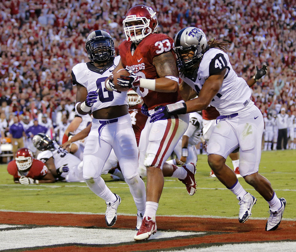 Photo - Oklahoma's Trey Millard (33) runs past TCU 's Elisha Olabode (6) and Jonathan Anderson (41) for a touchdown during the college football game between the University of Oklahoma Sooners (OU) and the Texas Christian University Horned Frogs (TCU) at the Gaylord Family-Oklahoma Memorial Stadium on Saturday, Oct. 5, 2013 in Norman, Okla.   Photo by Chris Landsberger, The Oklahoman