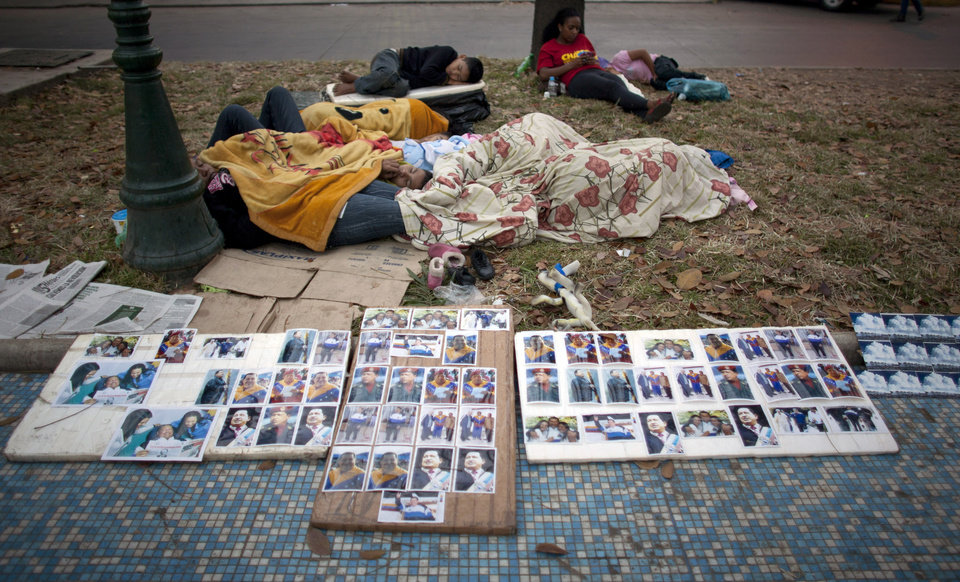 Photo - People rest outside the military academy where Venezuela's late President Hugo Chavez is lying in state in Caracas, Venezuela, early Sunday, March 10, 2013. People continue to parade to see the body of Chavez, who died of cancer on March 5. (AP Photo/Ariana Cubillos)