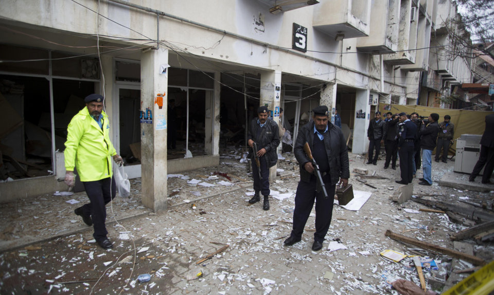 Photo - Pakistani police officers look for evidences at the site of a suicide attack in a court complex, Monday, March 3, 2014 in Islamabad, Pakistan. Two suicide bombers blew themselves up at the court complex, killing 11 people and wounding dozens in a rare terror attack in the heart of Islamabad, officials said. (AP Photo/B.K. Bangash)