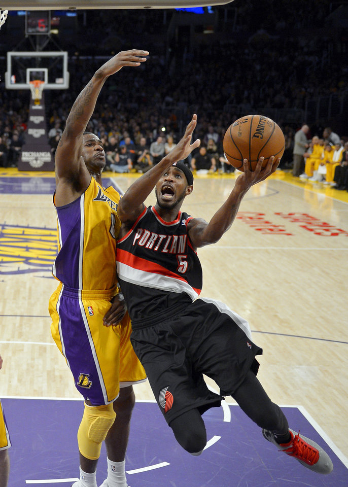 Photo - Portland Trail Blazers guard Will Barton, right, puts puts up a shot as Los Angeles Lakers forward Earl Clark defends during the first half of their NBA basketball game, Friday, Feb. 22, 2013, in Los Angeles. (AP Photo/Mark J. Terrill)