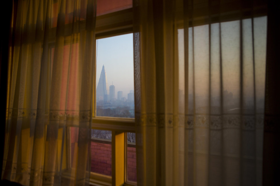 Photo - In this Feb. 21, 2013 photo, the 105-story Ryugyong Hotel is seen through the curtained window of the Potonggang Hotel in Pyongyang, North Korea. (AP Photo/David Guttenfelder)