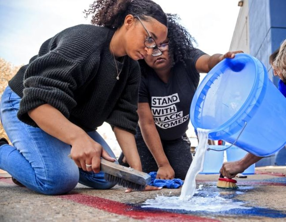 Photo -  Volunteers Jasmine Brown-Jutras, left, and Sache Primeaux-Shaw work to remove racist and homophobic symbols and language spray-painted on the building that includes the offices of the Oklahoma Democratic Party located at 3700 Classen Boulevard in Oklahoma City, Okla. on Thursday, March 28, 2019.  Photo by Chris Landsberger, The Oklahoman
