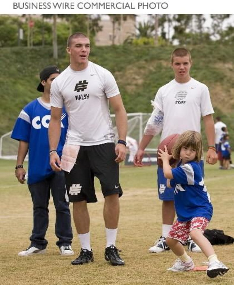 Quarterback J.W. Walsh from Denton (Guyer), Texas, looks on as Aska Taylor, age 6, from the Boys & Girls Club of Aliso Viejo works on her passing game at the ESPN Elite Quarterback Competition. (Photo: Business Wire)