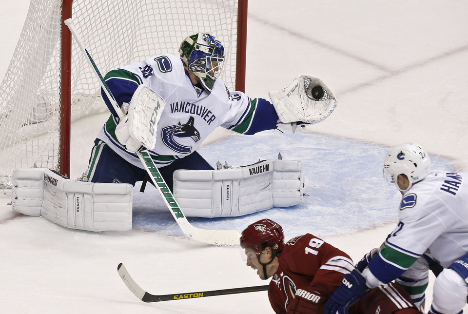 Vancouver Canucks' Cory Schneider, left, makes a glove save on a shot by Phoenix Coyotes' Shane Doan (19) as Canucks' Dan Hamhuis (2) defends during the second period in an NHL hockey game, Thursday, March 21, 2013, in Glendale, Ariz. (AP Photo/Ross D. Franklin)
